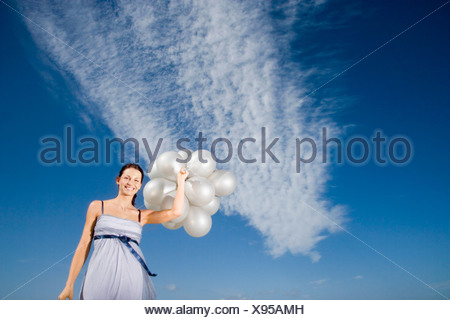Woman holding balloons against sky, portrait, low angle view Banque D'Images