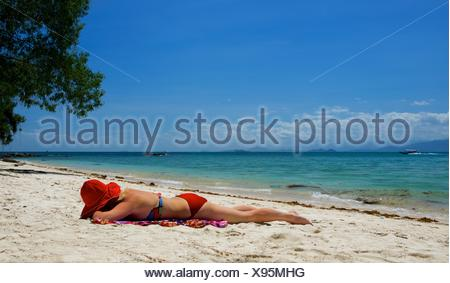 Femme en train de bronzer sur la plage, la Malaisie Banque D'Images