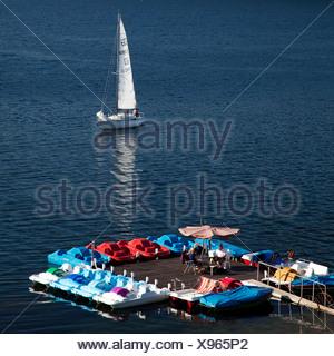 Un bateau à voile à proximité d'un service de location de bateaux à pédales sur le lac Sorpesee ou Sorpe, Langscheid, Sundern, Sauerland, Rhénanie du Nord-Westphalie Banque D'Images
