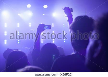 Vue arrière du groupe en club bras levés de filmer les concerts sur smartphone Banque D'Images