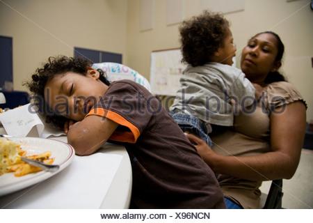 Selena Pina, une mère de quatre sans-abri et ses enfants font la queue pour recevoir un dîner préparé par les bénévoles de la promesse Banque D'Images