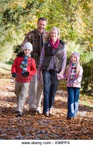Les grands-parents avec leurs petits-enfants à pied à l'extérieur dans park and smiling Banque D'Images