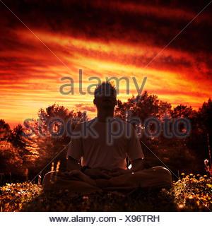Instructeur de Shaolin Kung Fu Shi Chang Dao méditant dans la nature pendant le coucher du soleil, assis les jambes croisées sous rouge spectaculaire Banque D'Images