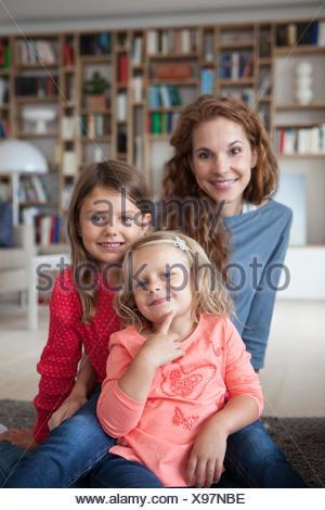 Portrait de deux petites soeurs et sa mère dans l'arrière-plan assis sur le plancher au salon Banque D'Images
