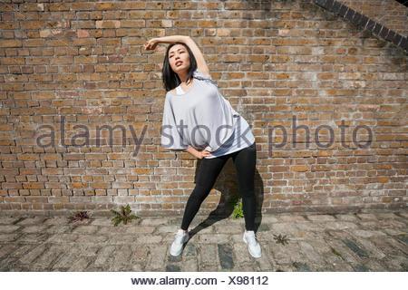 Toute la longueur de l'exercice s'étendant de la scène fit woman against brick wall Banque D'Images