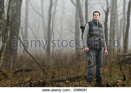 Un male hiker debout dans une forêt brumeuse de l'ouverture Banque D'Images