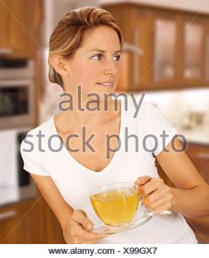 Femme dans la cuisine Boire une tisane Banque D'Images