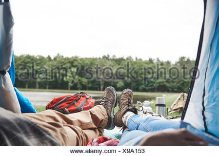 Young couple relaxing in tent, vue, low section Banque D'Images