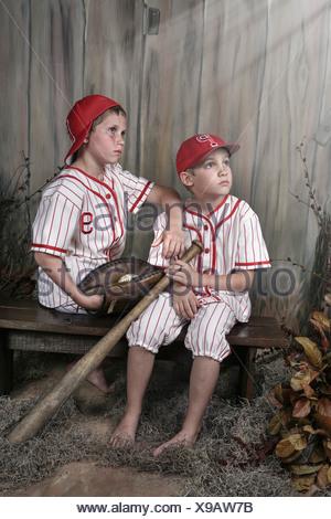 Deux garçons en uniforme de base-ball assis sur un banc Banque D'Images