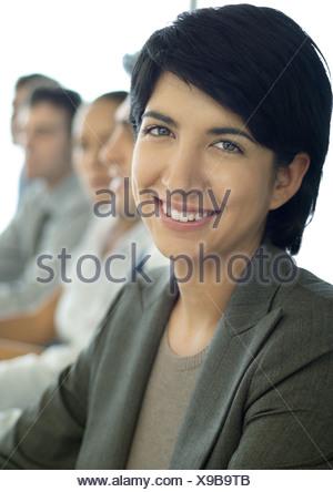 Businesswoman smiling at camera, collègues en arrière-plan Banque D'Images