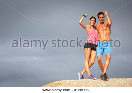 Couple flexing muscles sur boulder Banque D'Images