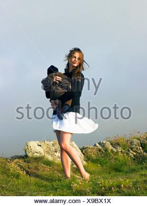 Jeune femme tenant le bébé avec le vent qui souffle sa jupe. Banque D'Images