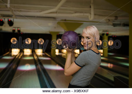 Portrait of smiling young woman bowling Banque D'Images