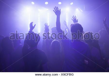 Vue arrière du groupe en concert regarder club bras levés Banque D'Images