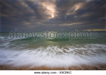 L'action des vagues et l'approche de l'orage. Lieu non identifié de sables bitumineux. Devon Banque D'Images