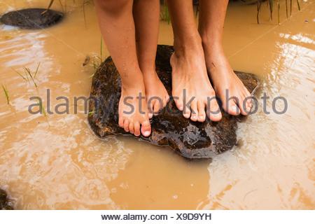 Pieds nus, debout sur un rocher dans l'eau trouble à currumbin creek; currumbin, Gold Coast, Queensland, Australie Banque D'Images