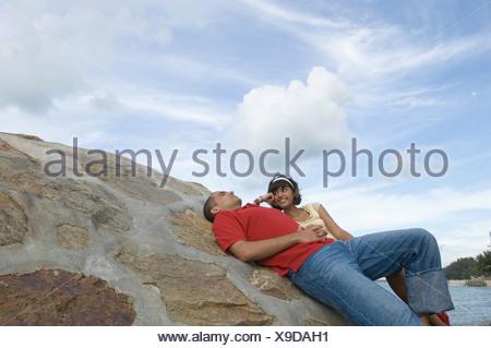 Jeune femme sur la plage avec un jeune homme souriant et Banque D'Images