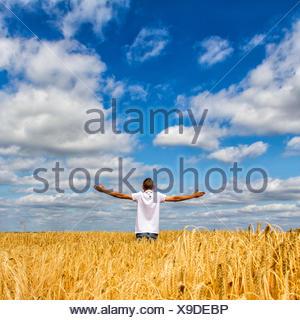 Vue arrière de l'Homme debout dans le champ avec les bras tendus