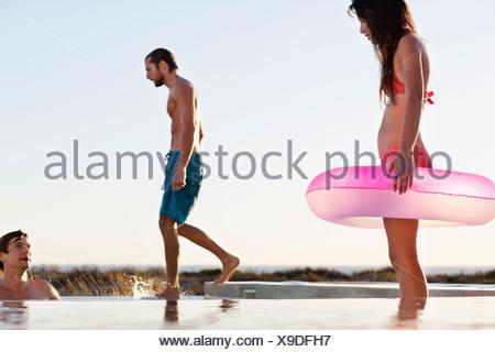 Femme debout avec un anneau gonflable dans une piscine Banque D'Images