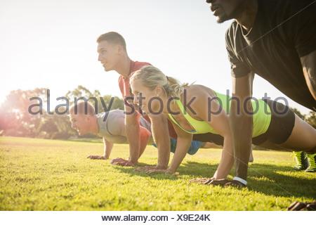 Groupe de jeunes adultes de faire des tractions dans le champ Banque D'Images