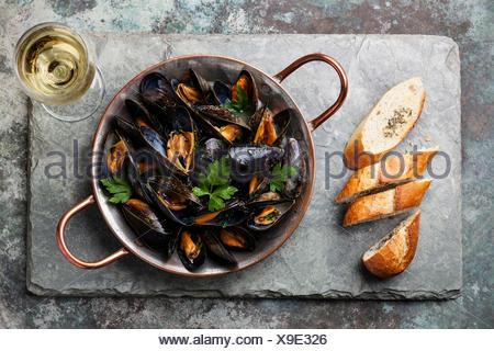Les moules dans un plat de cuisson en cuivre et baguette française avec des herbes sur fond ardoise