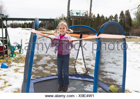Portrait of young girl jumping on trampoline dans park Banque D'Images