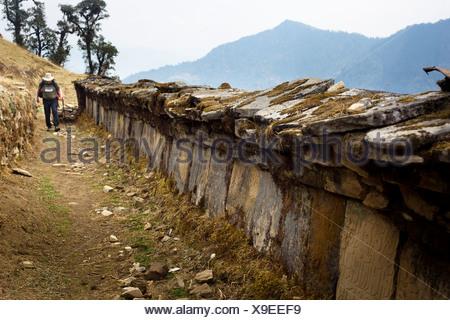 Un seul Canadien trekker marchant à côté d'un mur de prière de montagne au Népal. Banque D'Images