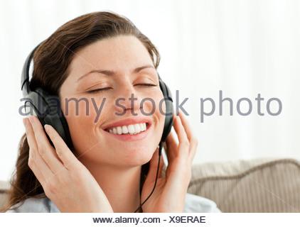 Joli portrait avec de la musique relaxante assise sur le canapé Banque D'Images