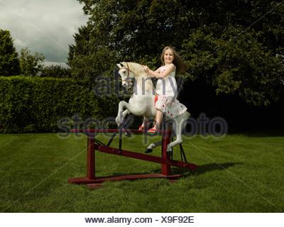 Une jeune fille sur un cheval à bascule Banque D'Images