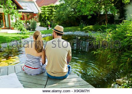 Couple hétérosexuel prend une pause par l'étang, vue arrière, Munich, Bavière, Allemagne Banque D'Images