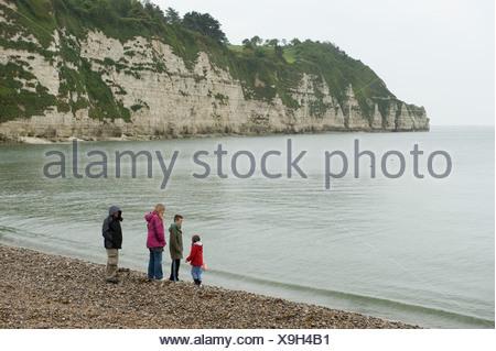 Famille de quatre personnes dans weathet sur vêtements humides comme sur une plage humide gret jour pluvieux de Devon Banque D'Images