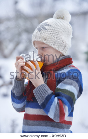 Boy in winter clothes drinking tea Banque D'Images