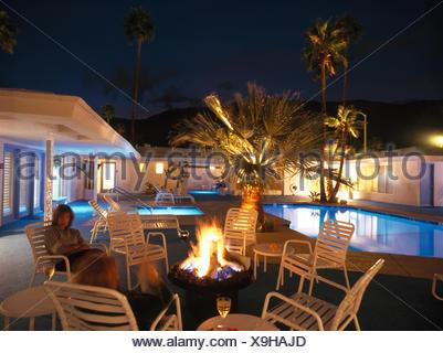 Deux femmes assises autour d'un foyer sur patio à côté de piscine de maison moderne dans la nuit Banque D'Images