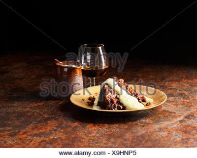 La vanille et sauce armagnac versé sur le pudding de Noël, un verre de brandy et le pot de sauce Banque D'Images