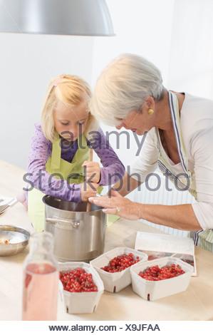 Fille avec grand-mère Cooking Jam Banque D'Images