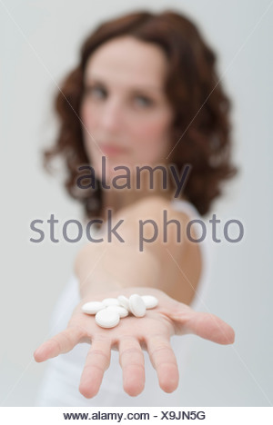 Mid adult woman showing white pills in hand Banque D'Images