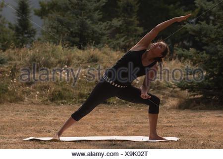 Fit woman performing exercice s'étendant sur un terrain ouvert Banque D'Images