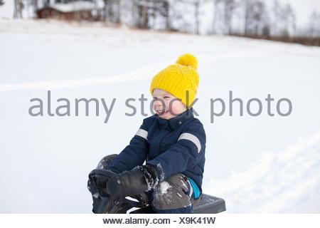 Jeune garçon assis sur le traîneau, dans paysage couvert de neige