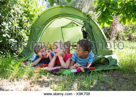 Trois enfants discutent dans la tente de jardin Banque D'Images