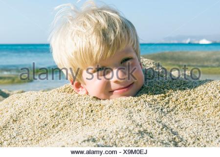 Jeune garçon enterré dans le sable en souriant. Banque D'Images