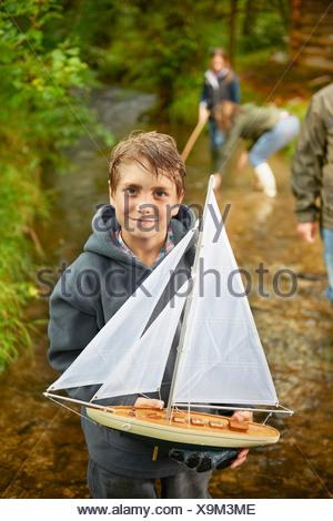 Young boy holding bateau à voile en rivière Banque D'Images