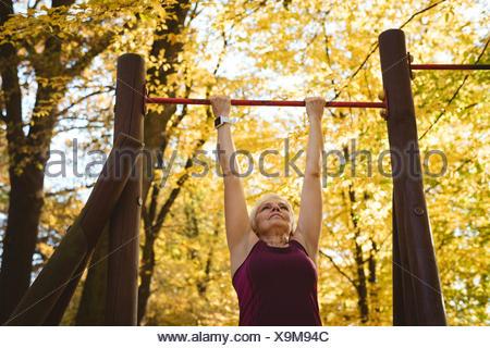 Senior woman pratiquer de l'exercice dans le parc Banque D'Images
