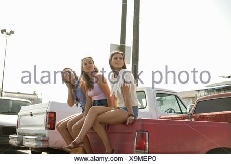 Trois jeunes femmes, assis à l'arrière du camion, à l'écart Banque D'Images