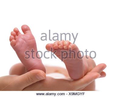 Les pieds de bébé nouveau-né sur la main de la mère