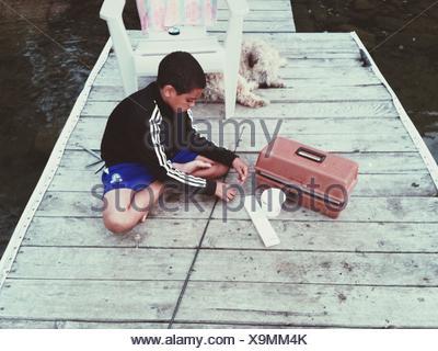 Garçon assis avec Canne à pêche On Jetty Banque D'Images