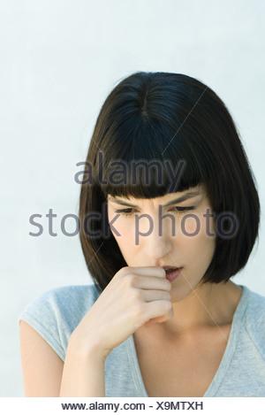 Woman biting pouce et regardant vers le bas, la tête et épaules, portrait
