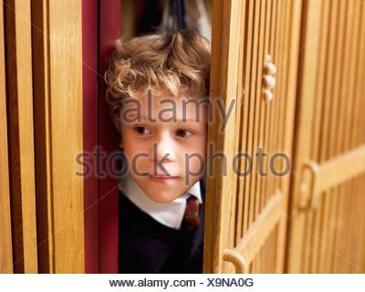 Boy (4-7) en se cachant dans le casier, close-up
