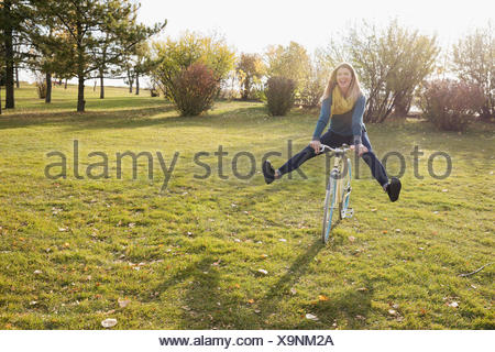 Femme espiègle riding bicycle in sunny autumn park Banque D'Images