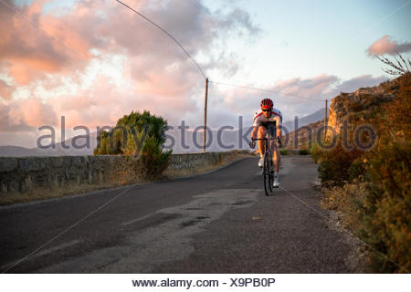 Homme en vélo le long d'une route côtière au coucher du soleil, Corse, France Banque D'Images