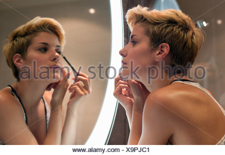 Woman applying makeup in mirror Banque D'Images